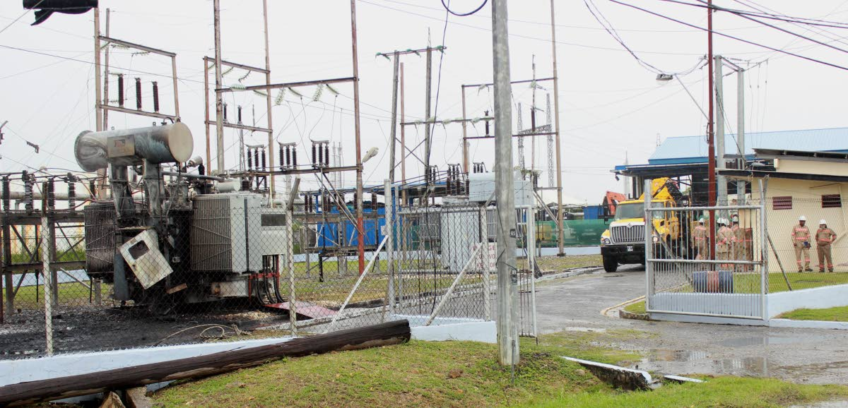 Fire out: TTEC workers, at right, shelter from the rain at an office near a substation which had been on fire earlier on Friday North Sea Drive, Point Lisas. PHOTO BY CHEQUANA WHEELER