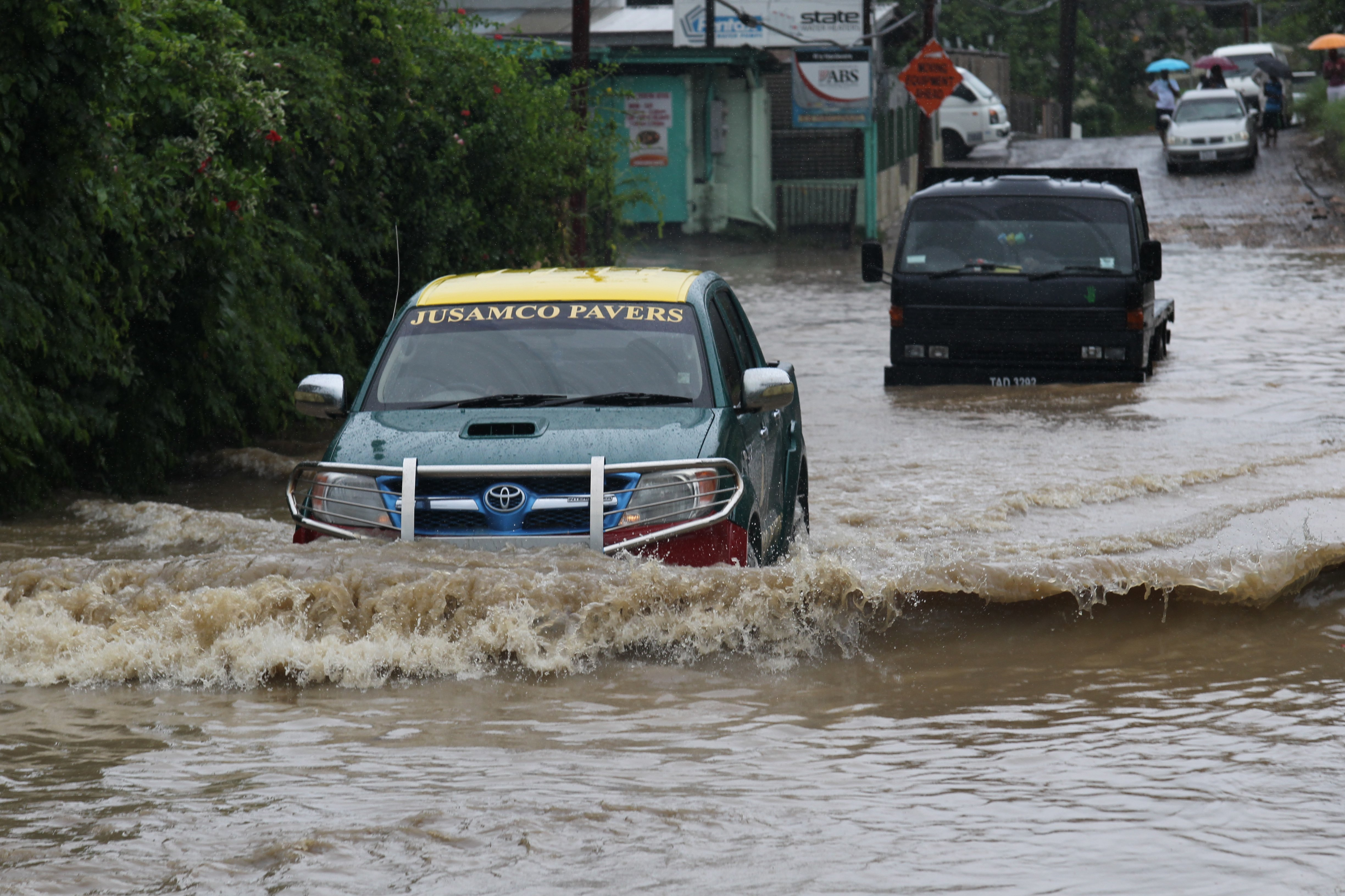 File photo: A pickup van maneuver  around a stalled truck in flood waters along the Macaulay main raod, Claxton bay as street and flash floods continue due to a weather system over Trinidad and Tobago.  Photo: Lincoln Holder