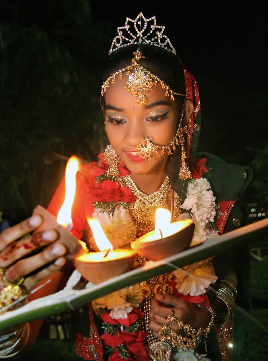 File photo: Rohini Mangru of St Johns Trace, Siparia lights deyas during Divali celebrations at the Botanical Gardens, Port of Spain last year.  Divali will be celebrated on November 6. FILE PHOTO/SUREASH CHOLAI