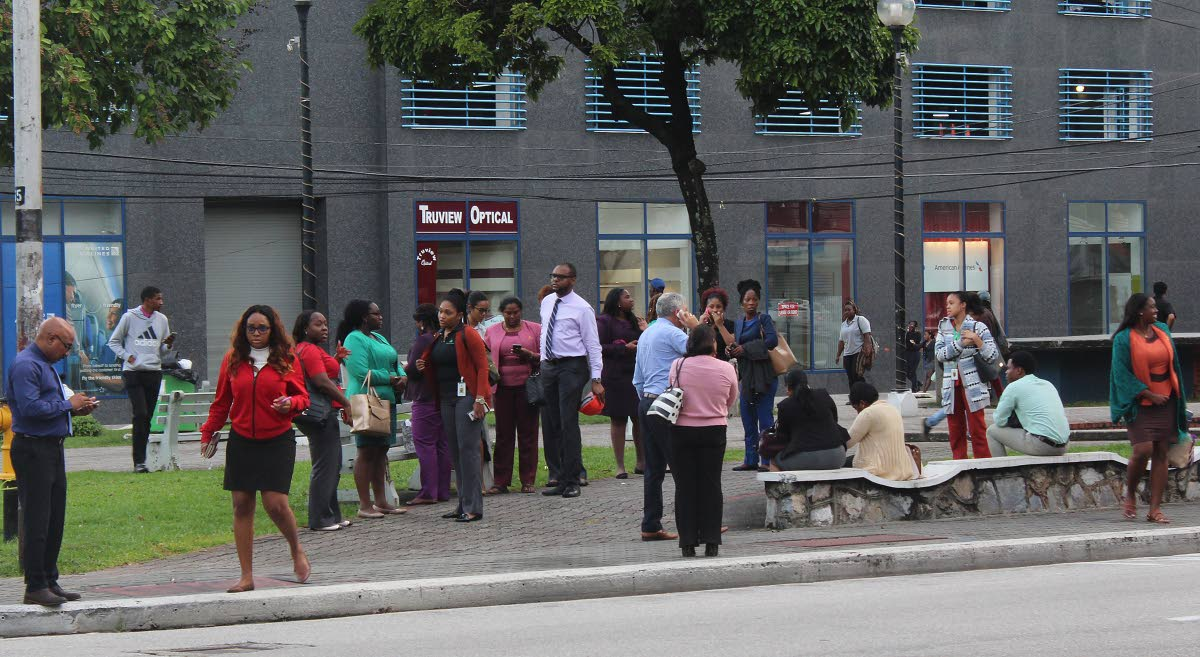 Workers from surrounding businesses assemble on Brian Lara Promenade, Port of Spain after a 6.9 earthquake on August 21. FILE PHOTO