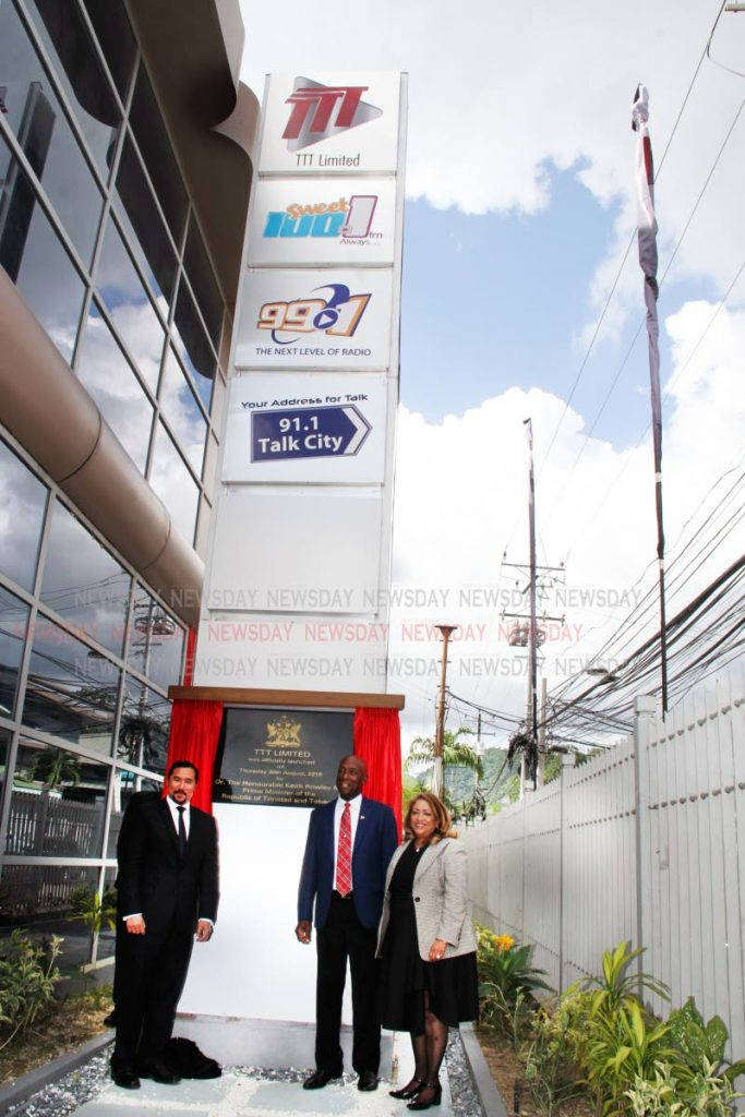 New beginning: Communications Minister Stuart Young, from left, Prime Minister Dr Keith Rowley and TTT chairman Lisa Agard stand alongside a new sign with the logos for TTT and three radio stations at Maraval Road, Port of Spain on Thursday. PHOTO BY SUREASH CHOLAI