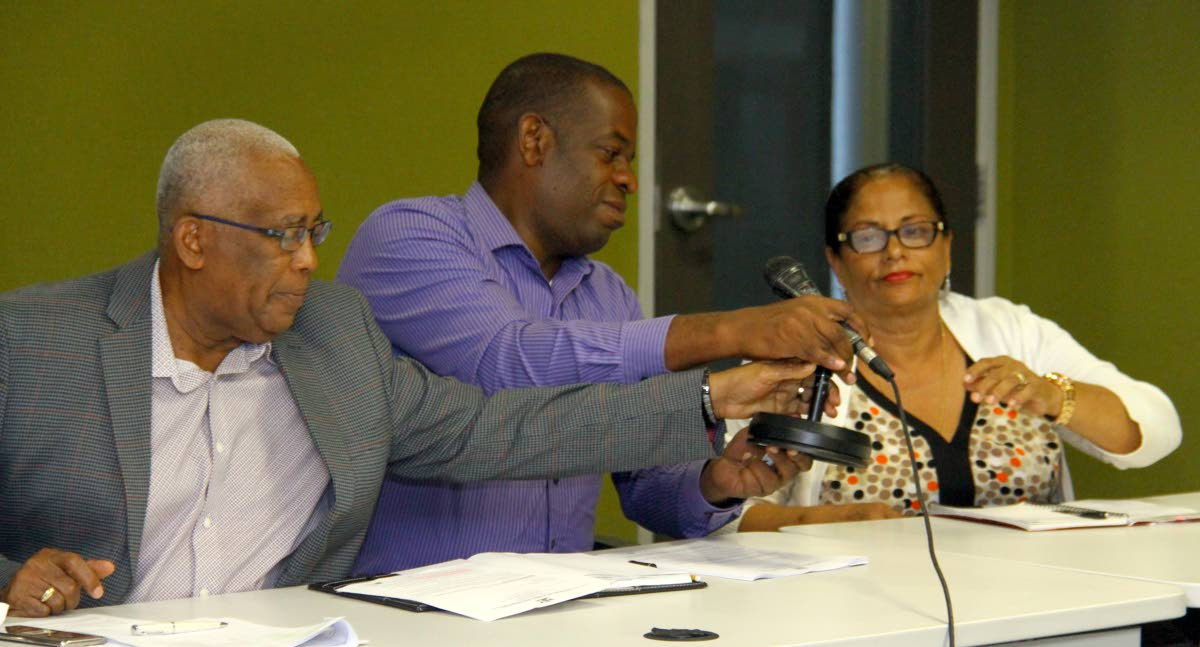 Over to you: Education Minister Anthony Garcia and Dr Lovell Francis, Minister in the Education Ministry, help to hand over the microphone to Raffiena Ali-Boodoosingh, president of the National Parent-Teacher Association during a press conference at the ministry, Port of Spain yesterday. PHOTO BY ROGER JACOB
