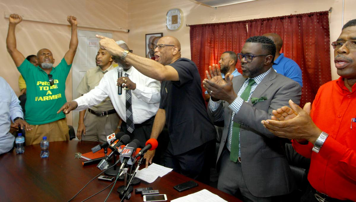 SAD AND SORRY: Shiraz Khan (left) gesticulates along with other union leaders on Monday at media conference, NUGFW, Upper Henry Street, PoS.