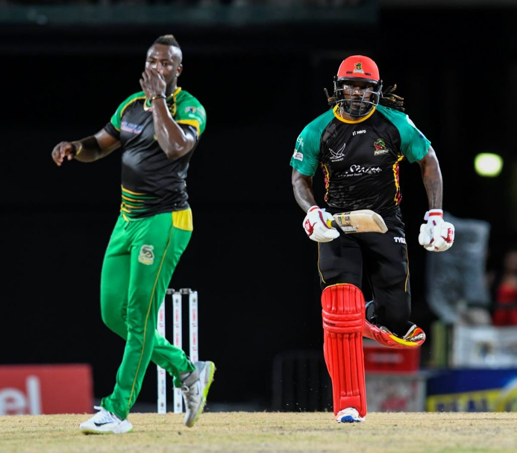 St Kitts and Nevis Patriots captain Chris Gayle, right, trots for a single as Jamaica Tallawahs skipper and bowler Andre Russell, left, looks on during a CPL match at Warner Park, St Kitts, Sunday. (Photo by Randy Brooks - CPL T20)