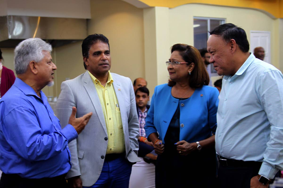 TALK SHOP: Opposition Leader Kamla Persad-Bissessar speaks with MPs Dr Bhoendradatt Tewarie, Dr Roodal Moonilal and David Lee after a press conference at the Passage to Asia restaurant in Chaguanas yesterday.