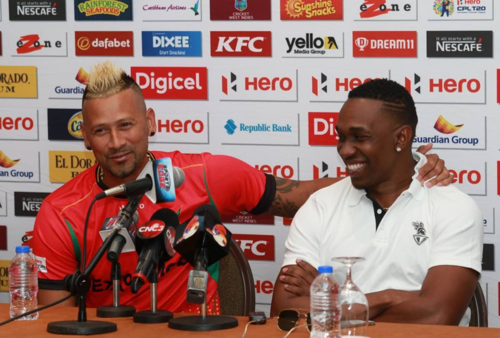 Guyana Amazon Warriors captain Rayad Emrit (left) and Trinbago Knight Riders captain Dwayne Bravo share a light moment during the Hero CPL press conference at the Hyatt Regency Hotel yesterday.