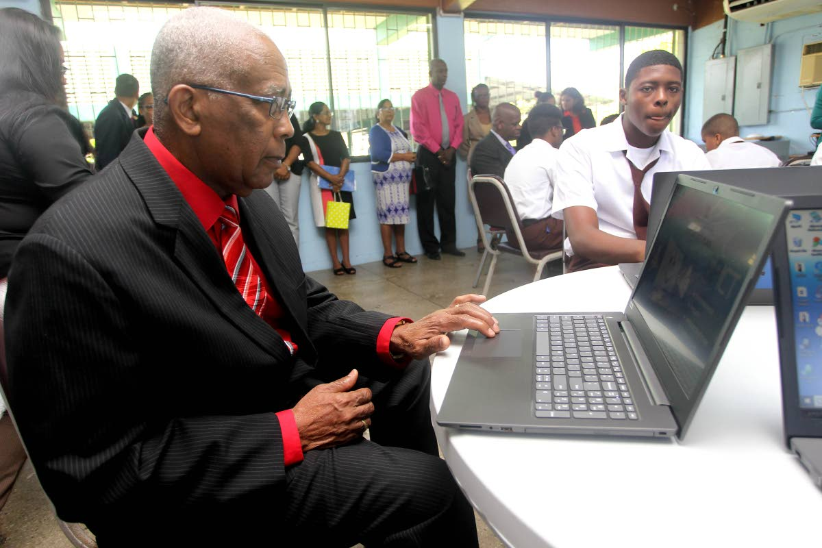 BACK TO SCHOOL: Education Minister Anthony Garcia tries out one of the laptops he and Minister in the Ministry Dr Lovell Francis presented to the Ste Madeleine Secondary School yesterday.