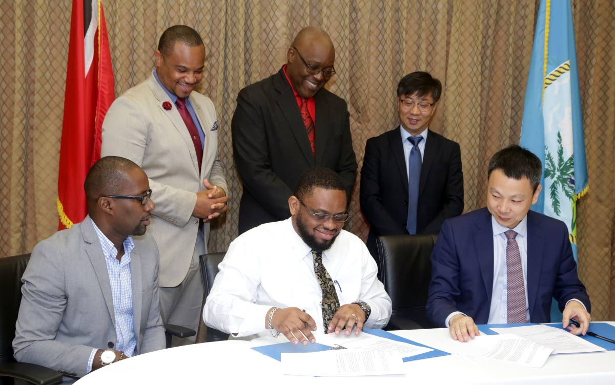 Ritchie Toppin, Administrator in the Division of Infrastructure, Quarries and the Environment, (front, centre) signs a Memorandum of Understanding (MOU) between the Tobago House of Assembly and the China Railway Construction Caribbean Co., Ltd (CRCCC) as executives look on. Looking on are, at right front, Yan Meng, Managing Director (CRCCC); front left, Dunstan Dennon, Advisor to the Secretary, Dunstan Denoon; Back (from left) Councillor Kwesi Des Vignes, Infrastructure Secretary; Kelvin Charles, Chief Secretary of the Tobago House of Assembly; and Mr. Feng Laigang, Vice President, CRCC International.