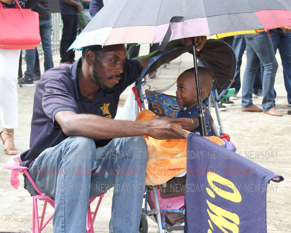 What's our fate?: Petrotrin labourer Daniel George in deep thought as his 11-month-old son, Micah, smiles at him outside the Office of the Prime Minister, St Clair last Thursday when Government told the OWTU it would proceed with the closure of the Petrotrin refinery.  PHOTO BY SUREASH CHOLAI
