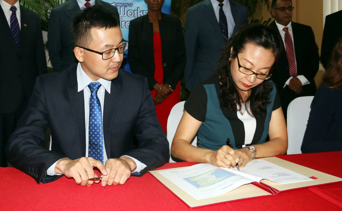 Xuewu Gao (left) and D Zhimin Hu of China Harbour Engineering Company sign the agreement to build a dry docking facility in La Brea. Rui Wang, senior business and regional manager of the Eastern Caribbean, CHEC Americas Division, projected that the project will generate foreign exchange in excess of US$500 million.