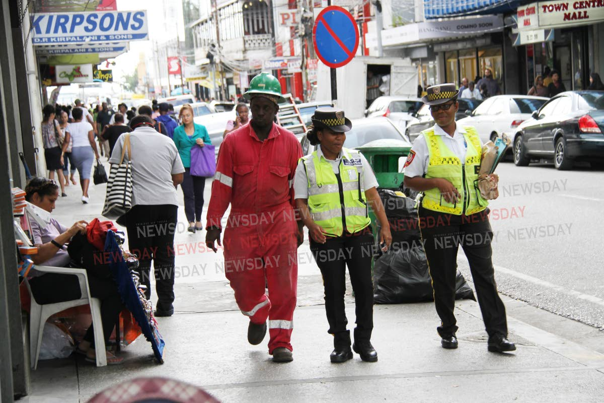 File photo: Traffic wardens and a construction worker walk along Frederick Street, Port of Spain.  PHOTO BY SUREASH CHOLAI