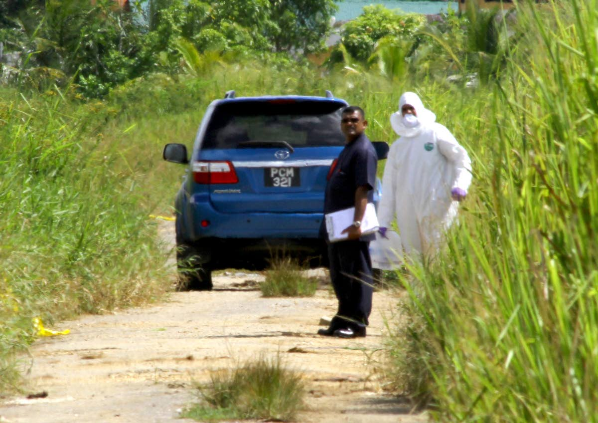Police stand near the car in which the body of a man was found at Warren Road, Cunupia.