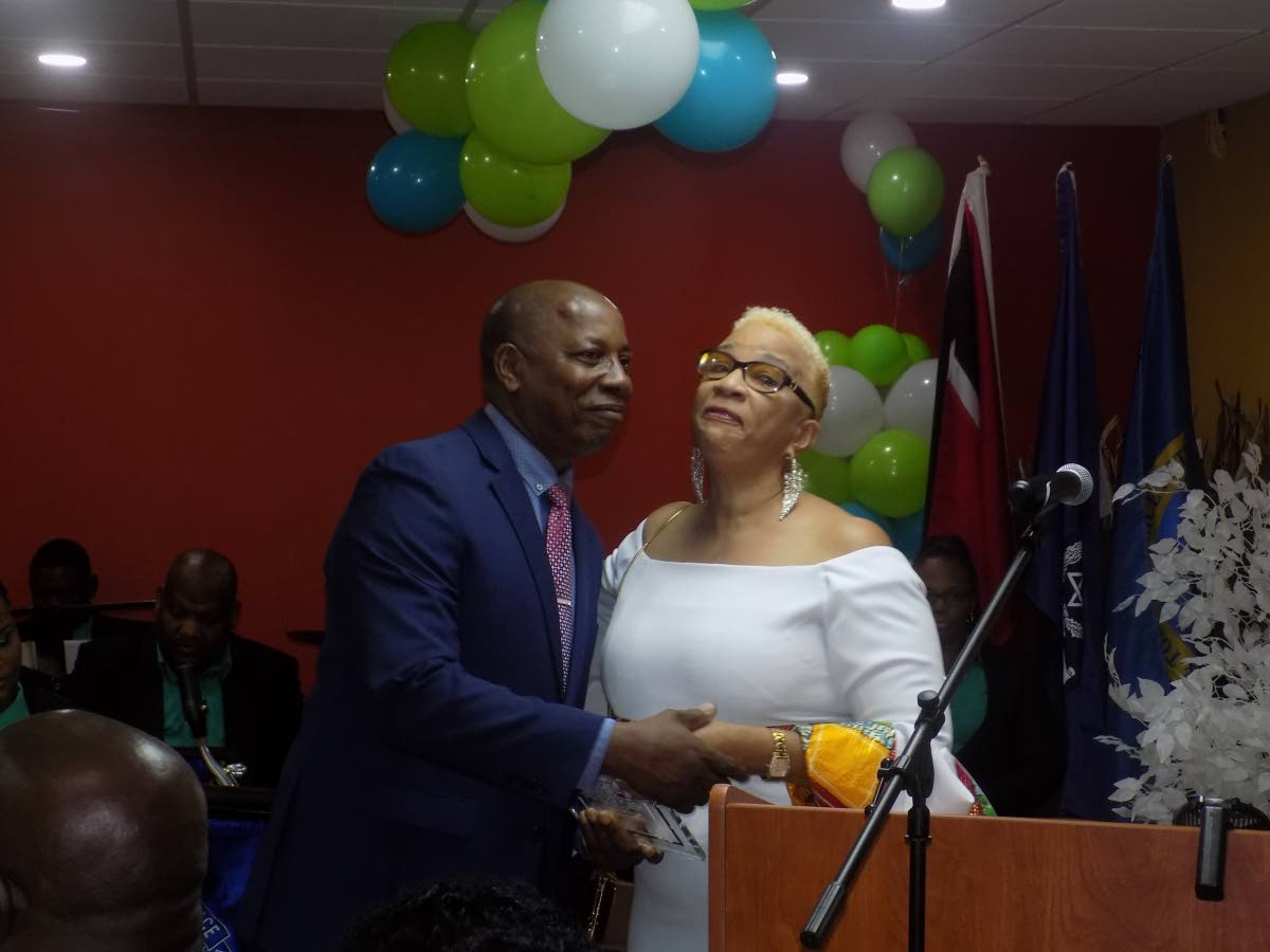 Former acting police commissioner Stephen Williams, left, kisses secretary general of the TT Police Service Retiree's Association Julie Carrington as he receives an award at a retirement dinner in Port of Spain yesterday.