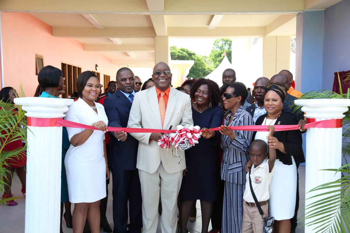 Chief Secretary Kelvin Charles cuts the ribbon to commission the newly built Scarborough RC School at Smithfield on August 23.  At left is Sports Minister and MP for Tobago West, Shamfa Cudjoe.