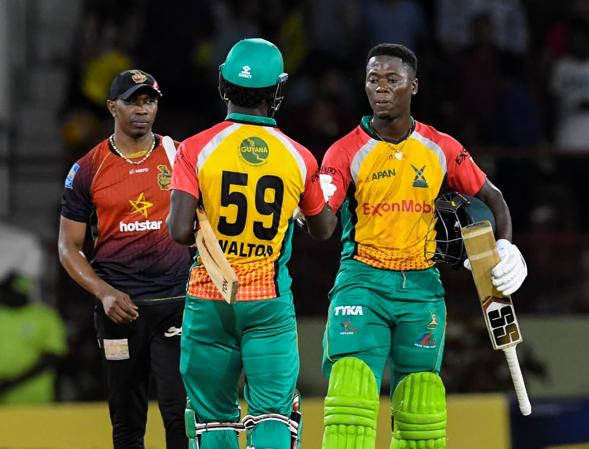 Trinbago Knight Riders captain Dwayne Bravo, left, watches as Guyana Amazon Warriors' Sherfane Rutherford, right, and Chadwick Walton celebrate victory in their final preliminary match of the Hero Caribbean Premier League at Providence Stadium, Guyana, Sunday. PHOTO BY RANDY BROOKS - CPL T20