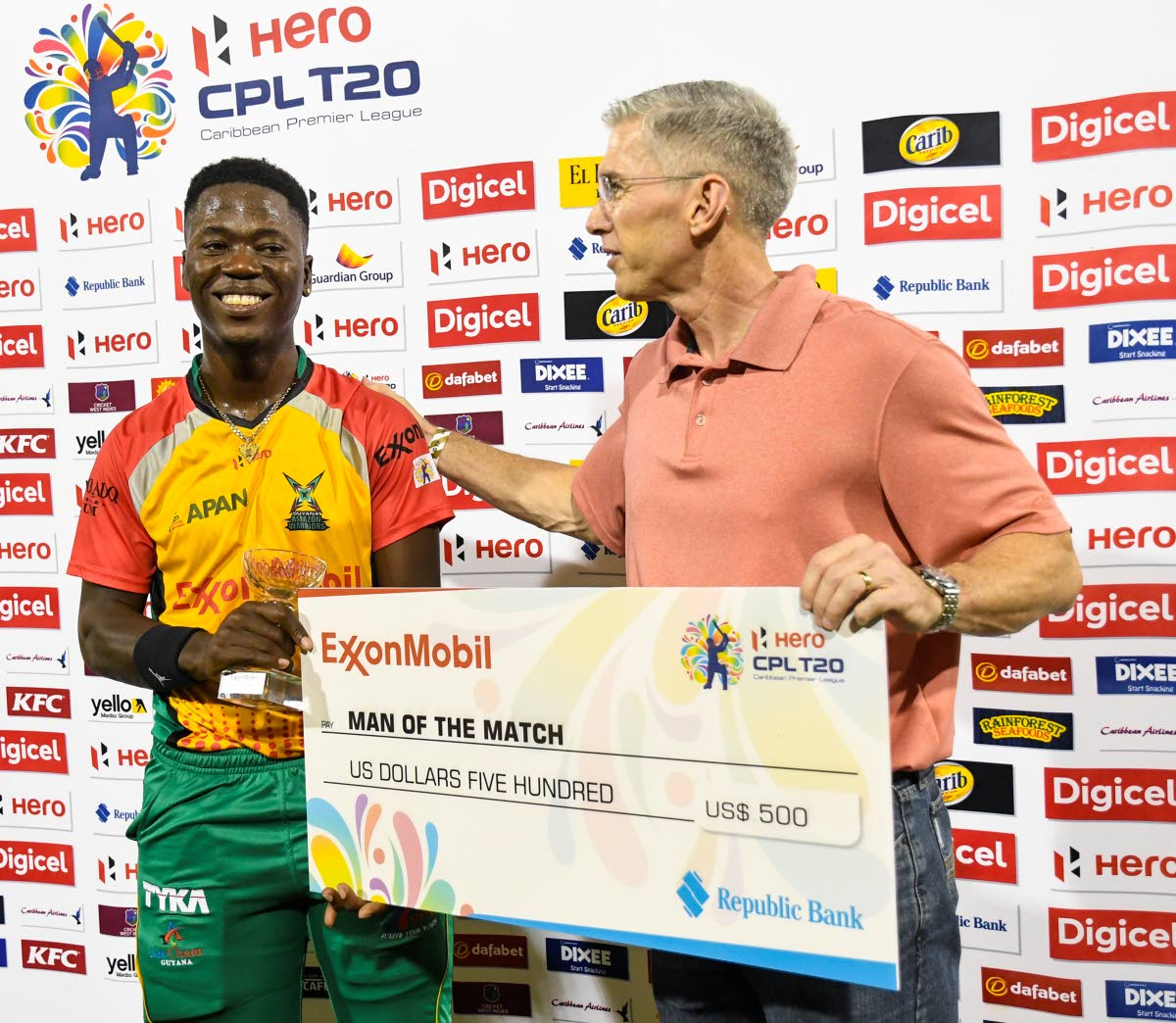 Sherfane Rutherford, left, of Guyana Amazon Warriors receives the man of the match prize from Rod Henson of Exxon Mobile after Guyana defeated Trinbago Knight Riders on Sunday at Providence Stadium in the Hero Caribbean Premier League. PHOTO BY RANDY BROOKS - CPL T20