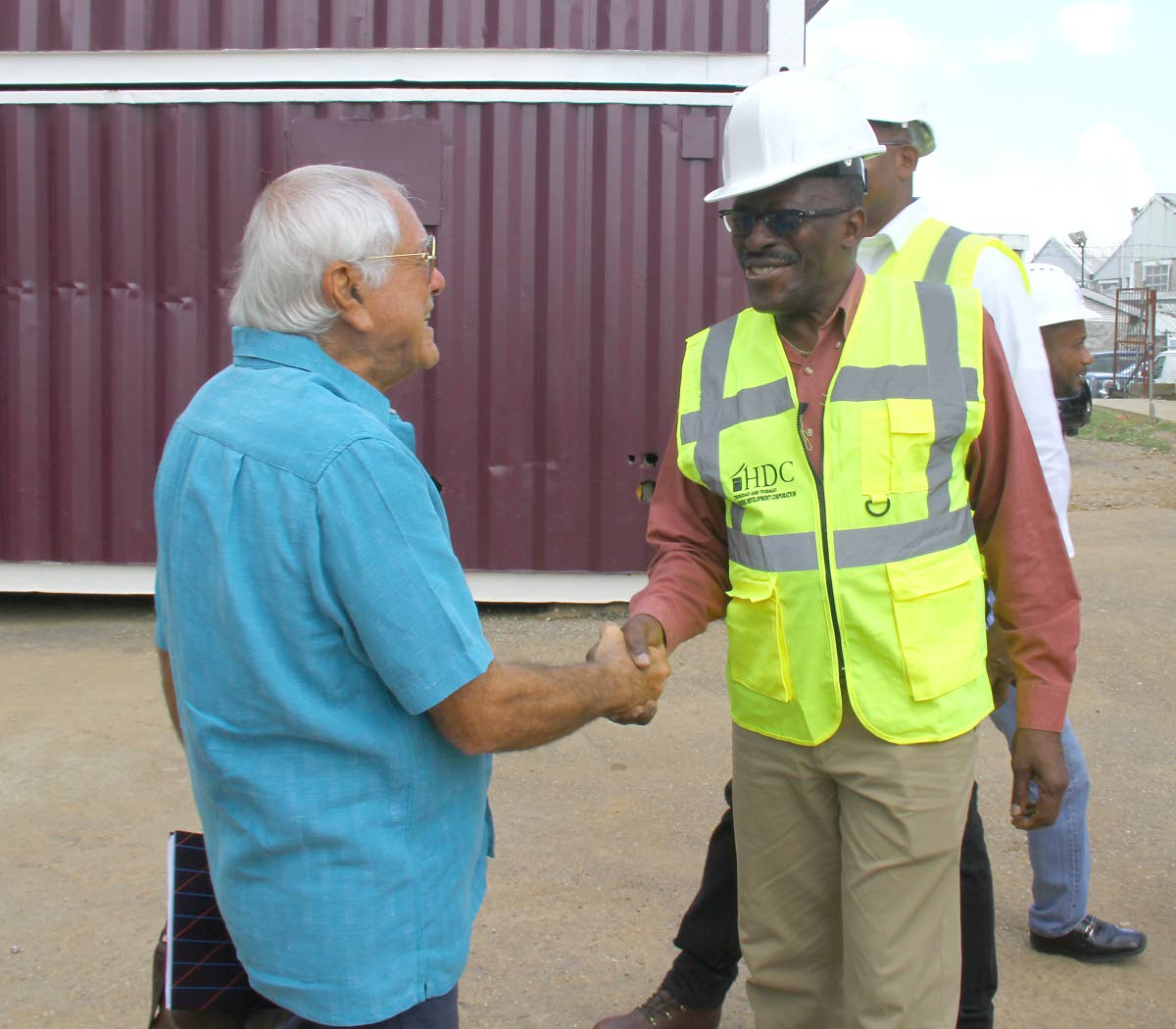 HEY THERE: Housing Minister Edmund Dillon, right, greets NH (International) chairman Emile Elias yesterday during a tour of a HDC site which is under construction in Mt Hope. PHOTO BY ROGER JACOB