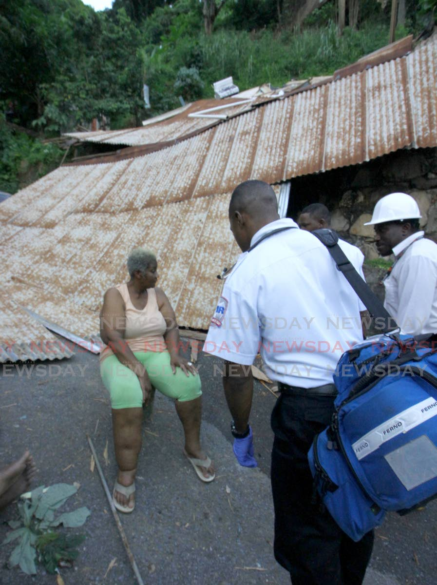UNHARMED: Great grandmother Viola King speaks to medics in front of the roof of her La Puerta, Diego Martin house which collapsed yesterday. PHOTO BY ROGER JACOB