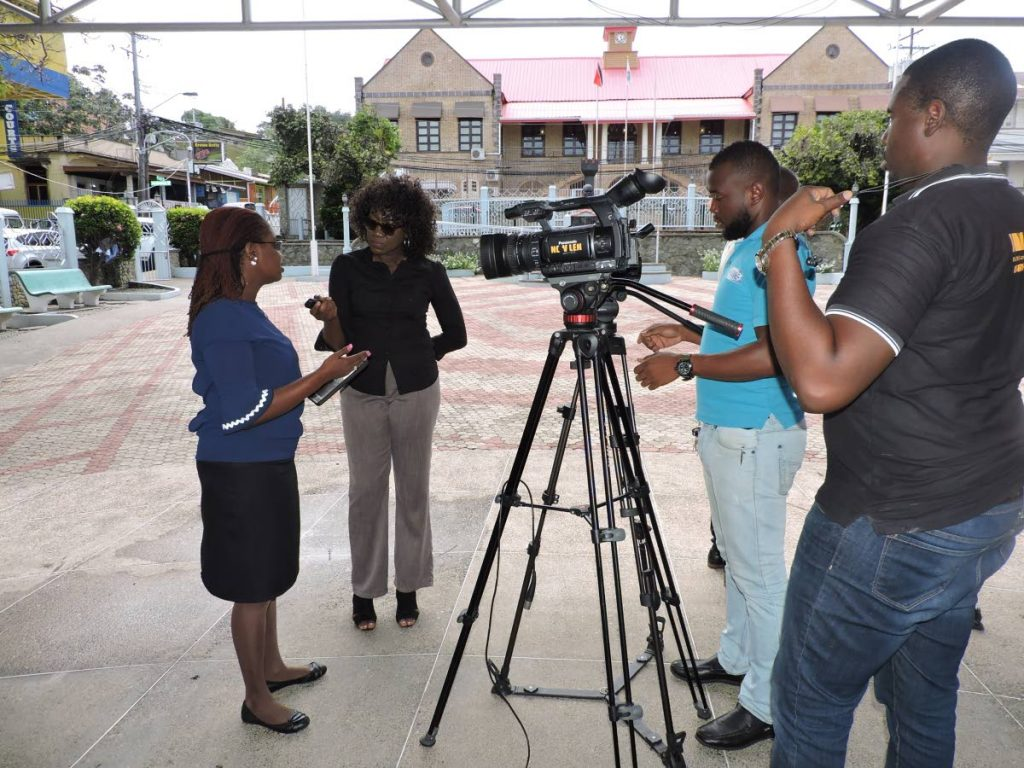 Minority Councillor Dr Faith BYisrael, left, conducts a press conference at James Park, Scarborough. In the background is  the Tobago House of Assembly Chamber.