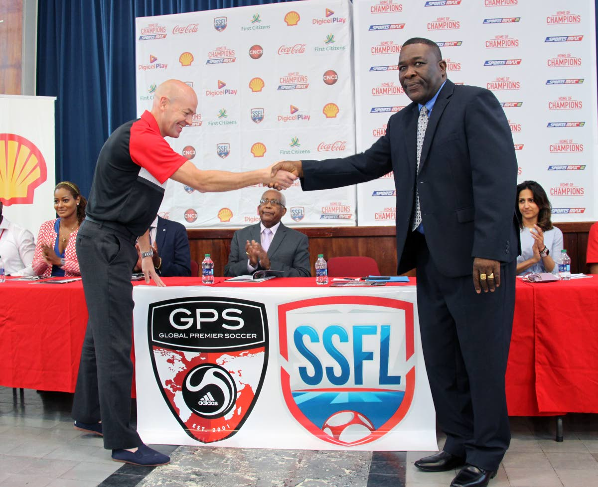 NEW PARTNERS: William Wallace, right, president of the Secondary Schools Football League, shakes the hand of Global Premier Soccer CEO Joe Bradley at the launch of this year's league at Fatima College in Mucurapo, yesterday. Education Minister Anthony Garcia, middle, applauds the partnership as Sports Max's Tanya Lee and Shell's Kellie-Marie Patel look on.