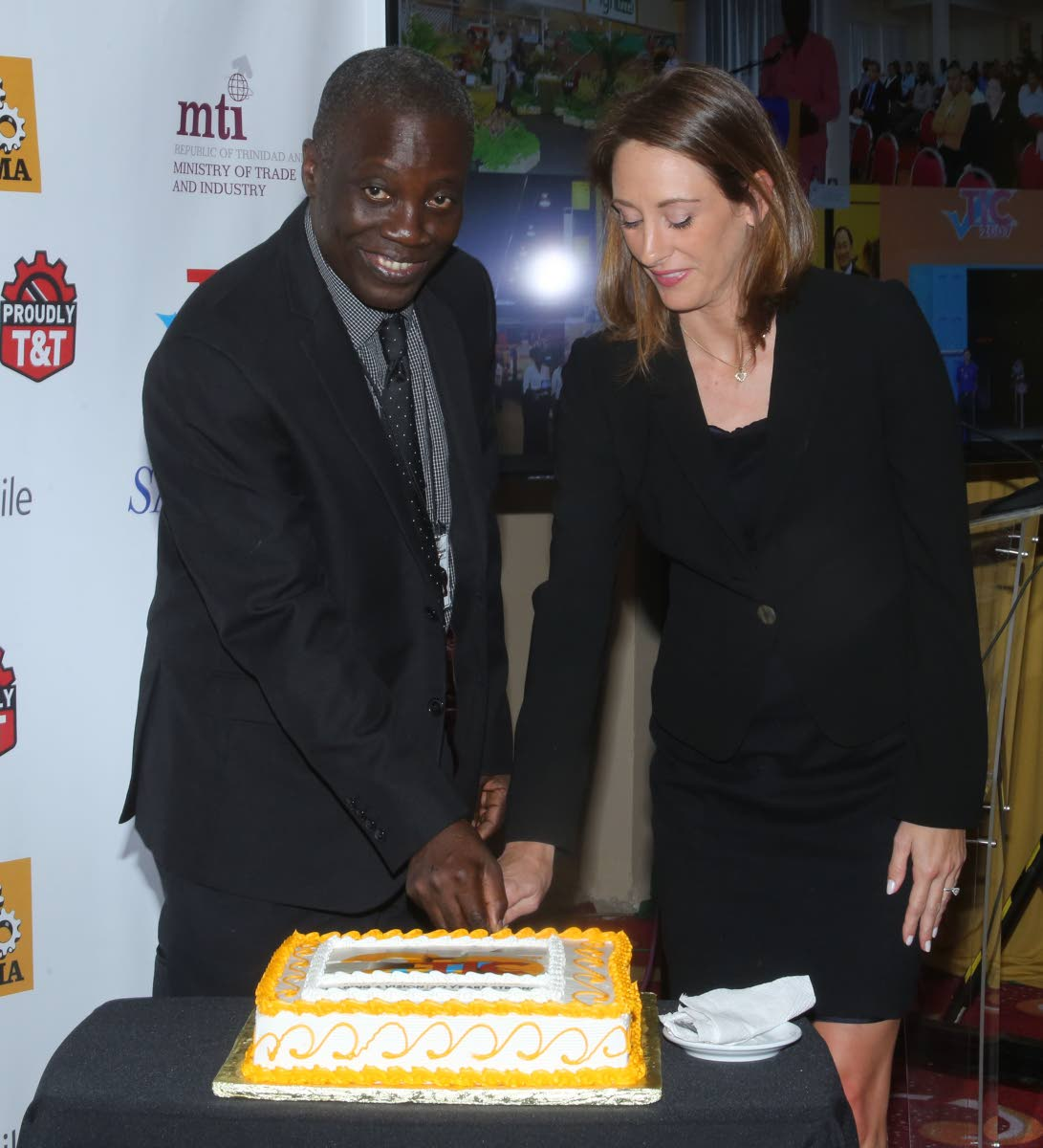 Permanent secretary in the Trade and Industry Ministry Norris Herbert and first vice president of the TT Manufacturers Association Franka Costelloe cut a cake to mark the anniversary of the Trade and Industry Convention at the launch of TIC 2019. Photo by Vashti Singh