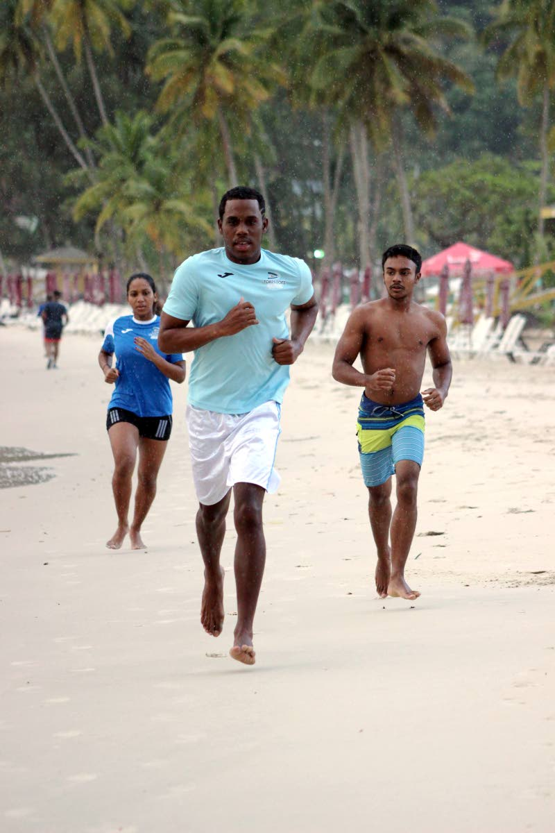 Torpedoes Swim Team members Virsnelit Faure (from left) Xavier Razac and Alex Ali run along the Maracas Bay shore as they prepare for the ASATT Subway Maracas Open Water swim event. Photo courtesy Torpedoes Swim Team