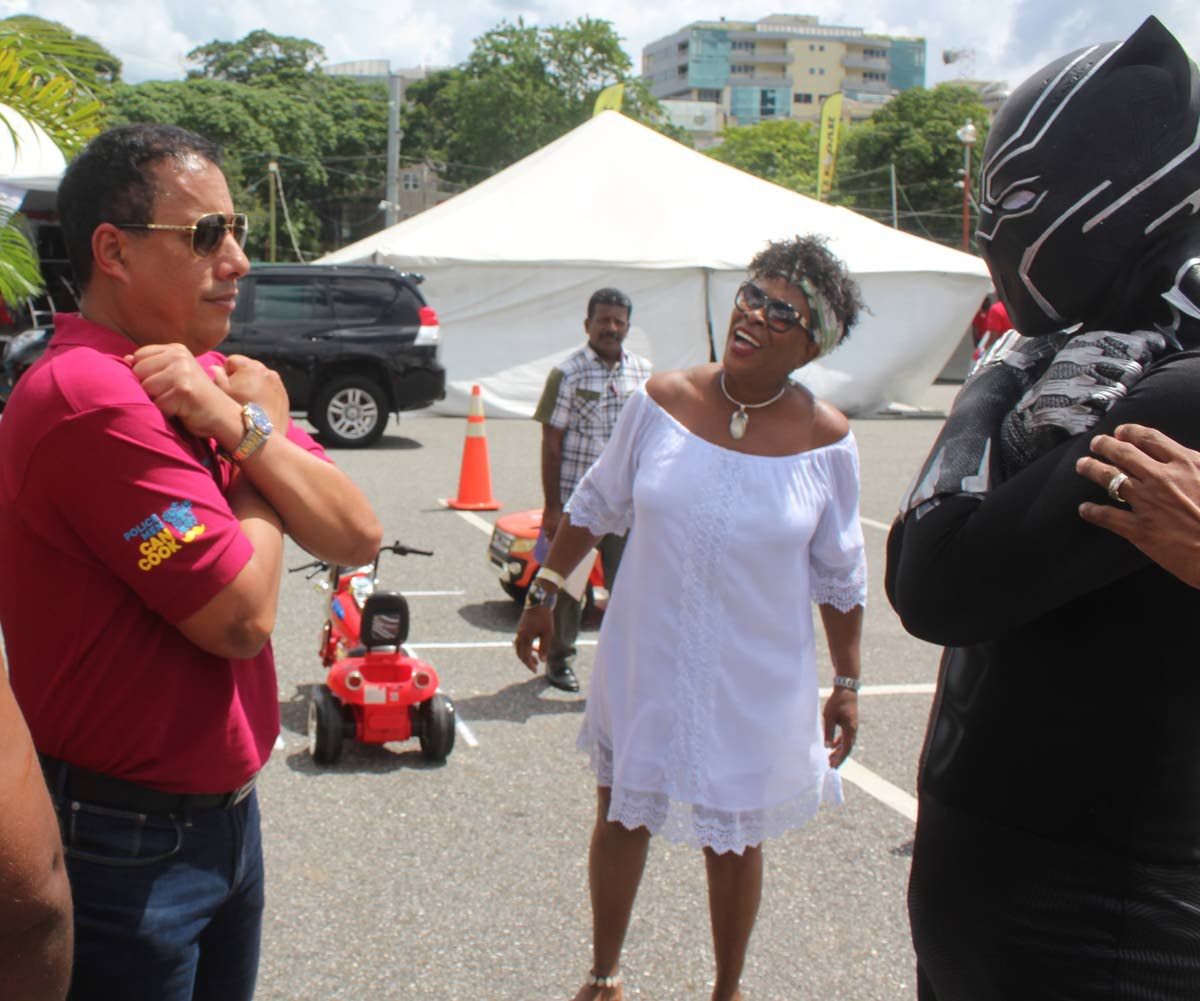 Police Commissioner gives the Wakanda forever sign to Black Panther, a portrayal of the superhero by police officer Christian Felician, during the Police Men Can Cook competition, Queen's Park Savannah, Port of Spain yesterday. PHOTO BY ENRIQUE ASSOON