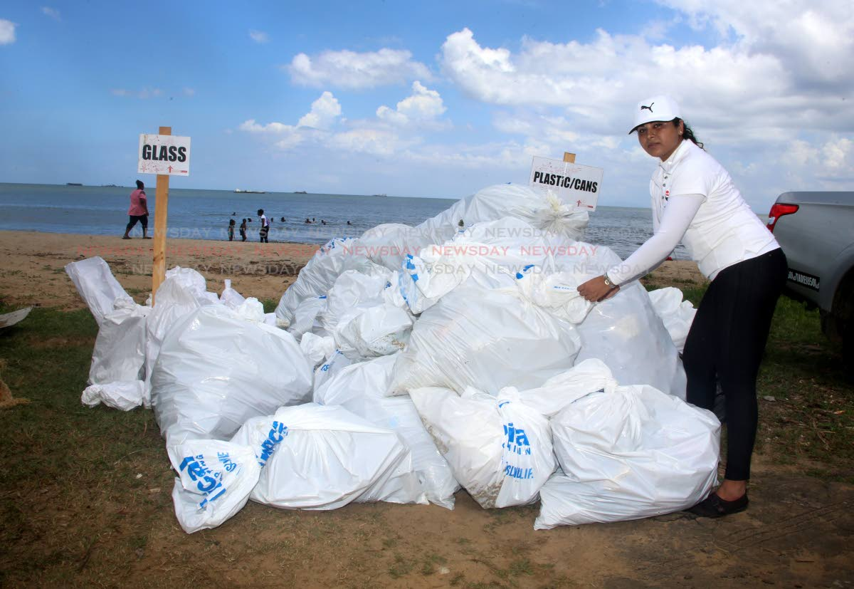 NGC employee Kavita Harry stacks garbage bags as part of a clean-up of Station Beach, La Brea.