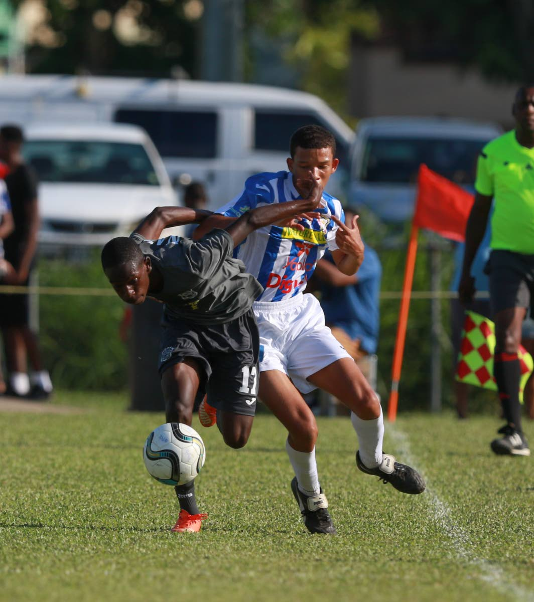 Naparima's Nathaniel Perouse(L)  tries to hold off  his opponent from CIC player during SSFL action at St Mary's grounds yesterday.