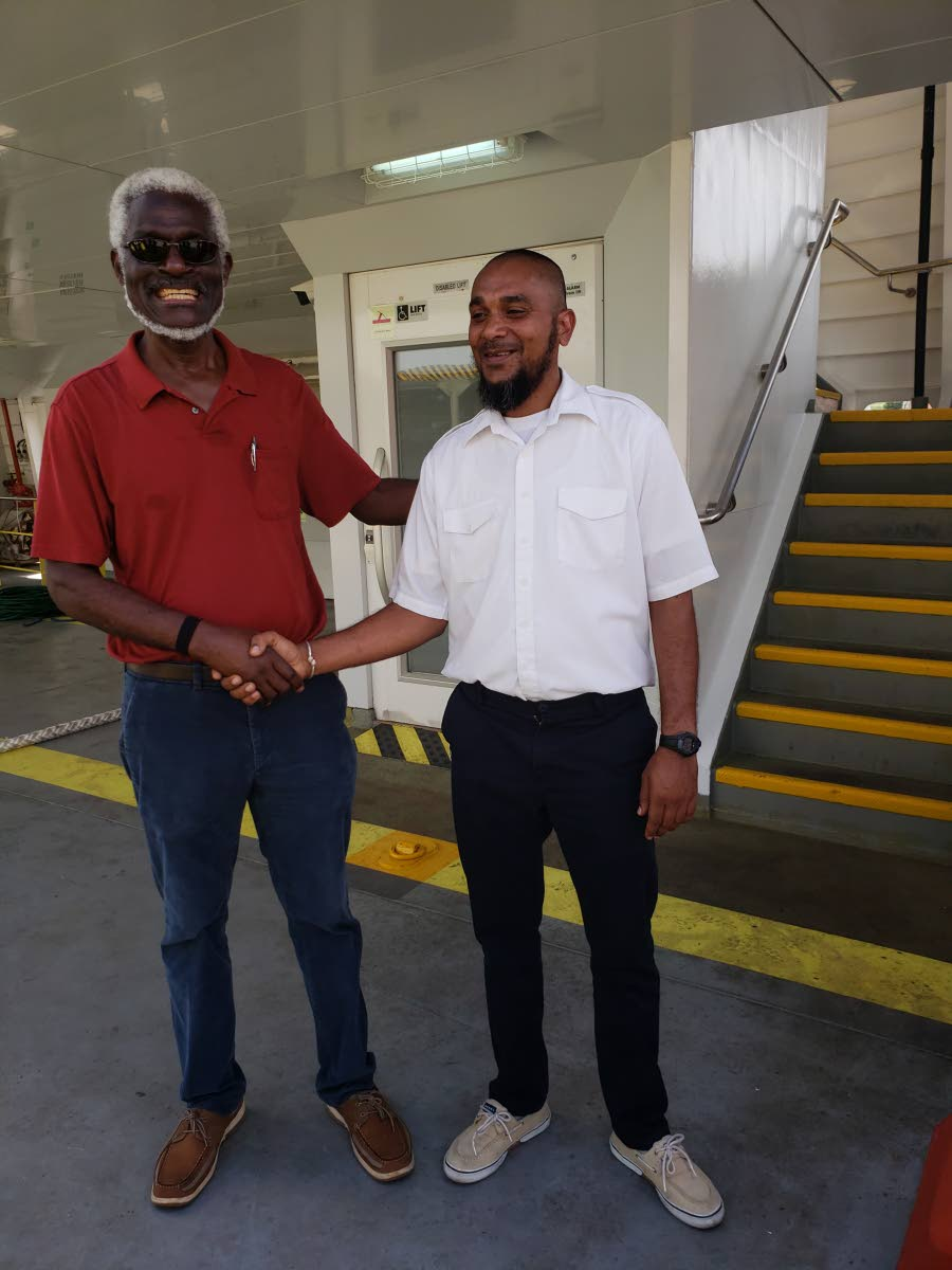 File photo: NIDCO's Chairman Herbert George, left, shakes hands with Allister Khan, local captain aboard the Galleons Passage following its second trial run to Tobago last September.