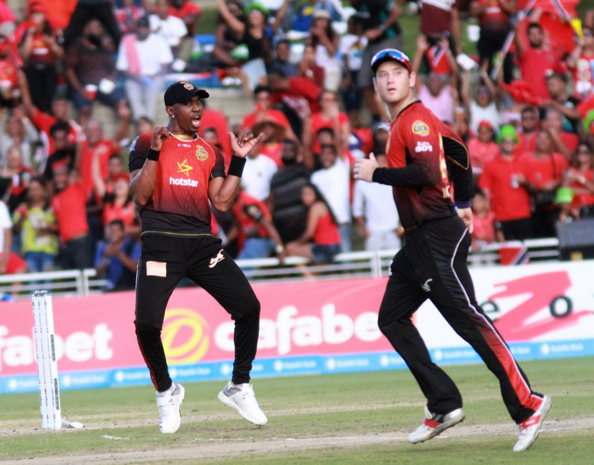 DANCING DJ: Trinbago Knight Riders captain Dwayne Bravo, left, celebrates a wicket in the Hero Caribbean Premier League final at the Brian Lara Academy in Tarouba, Sunday.