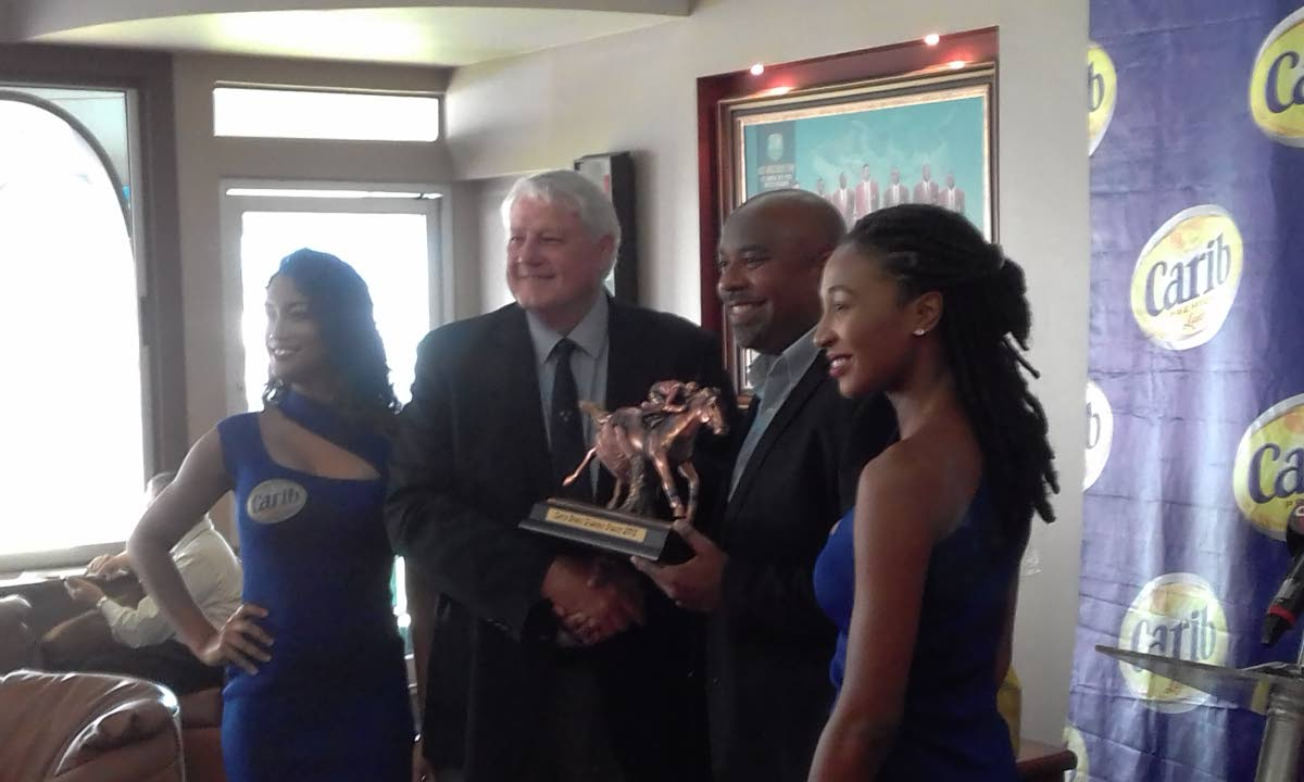 Arima Race Club (ARC) president Brian Stollmeyer (second from left) receives the Carib Brand Diamond Stakes trophy from Antron Forte, marketing manager of Carib Brewery Limited, while a pair of Carib models look on, during yesterday's media conference.