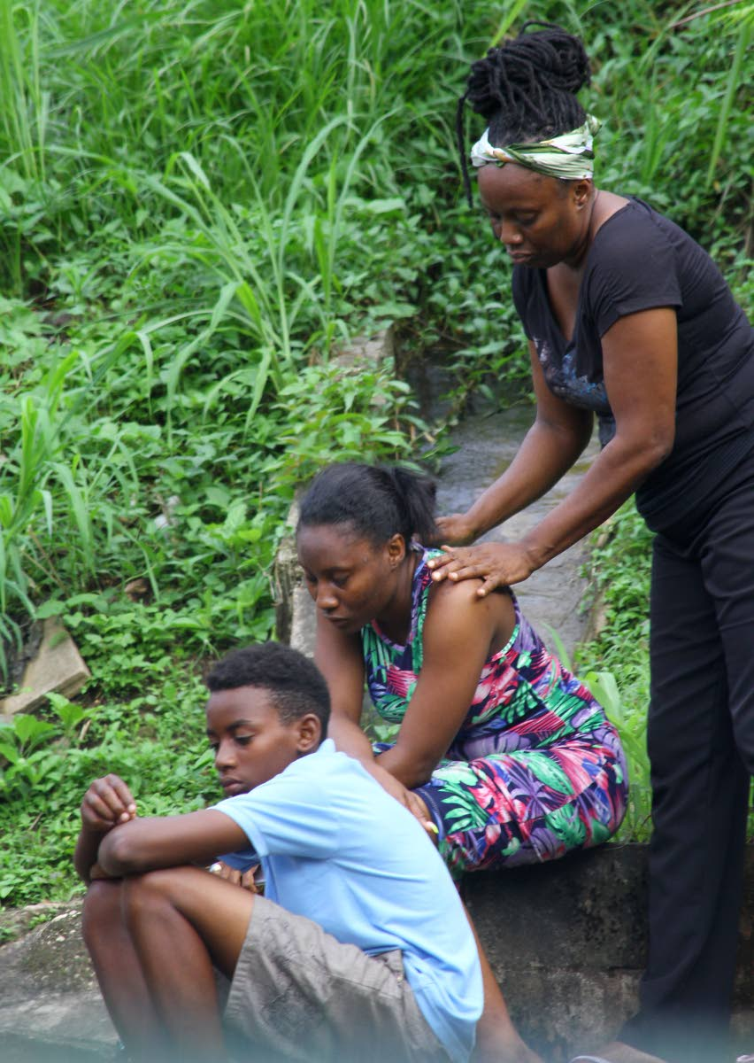 SORROW: People console each other on hearing the news that elderly siblings Victor Hutchinson, 78, and Claudette Cassell, 81, were found chopped to death yesterday in Cassell's house in Chinapoo Village, Morvant. PHOTO BY ROGER JACOB