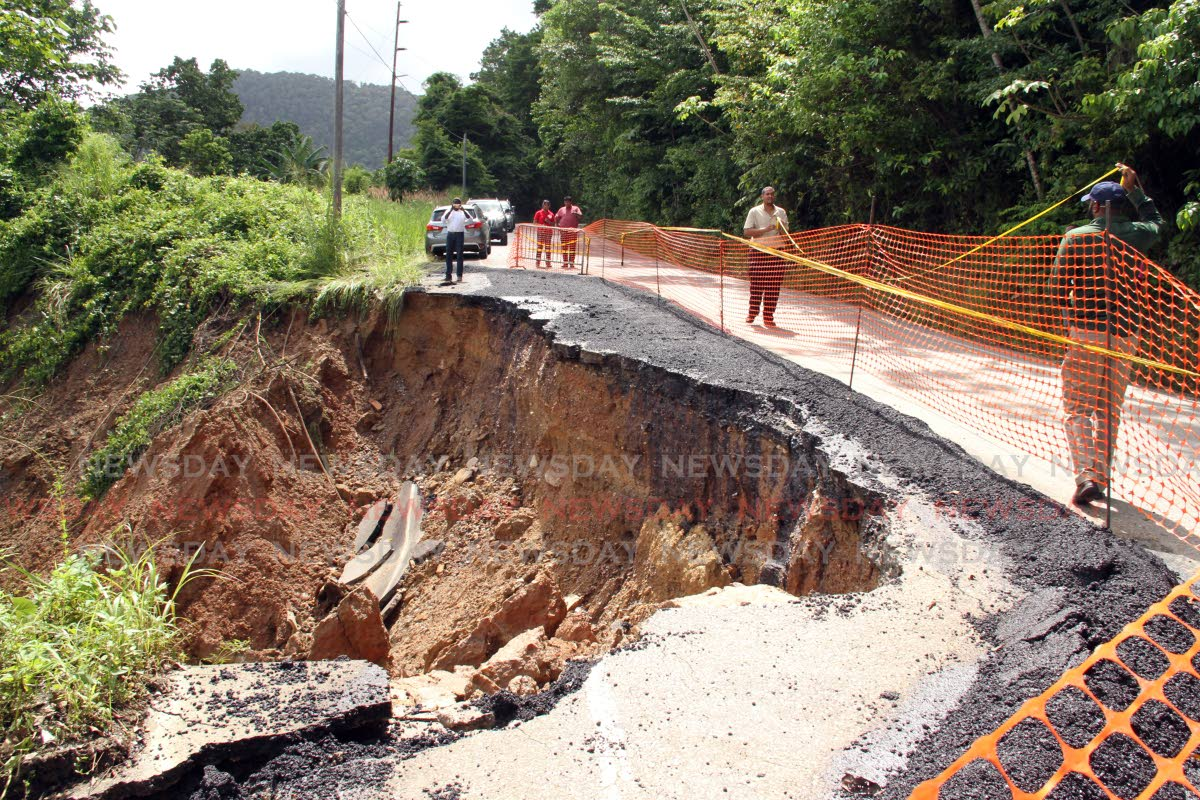 Officials of the Ministry of Works along the North Coast road just  before Maracas beach where a hugh section of the roadway  has  slip away after heavy rainfall earlier in the week, only one way traffic can proceed at this time. PHOTO SUREASH CHOLAI