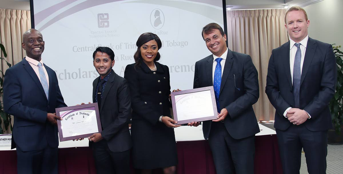 SCHOL WINNERS: Central Bank Governor Alvin Hilaire, left, presents a plaque to scholarship winner Shane Musai while De La Rue regional director and GM for Latin America and the Caribbean Fabio Ongarato, 2nd from right, presents a plaque to fellow school winner Zwena Carrington yesterday at the Central Bank in Port of Spain. At right is Gareth Evans, De La Rue currency regional manager. 
