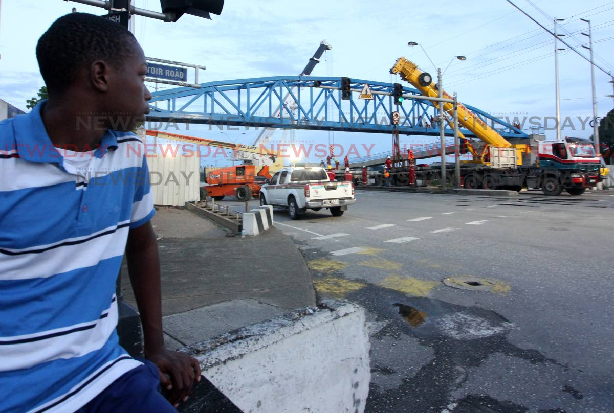 Super overpass: Carlon Haynes looks on as the Sea Lots pedestrian overpass is installated by crews over the Beetham Highway, near the Central Market, yesterday. PHOTO BY ROGER JACOB