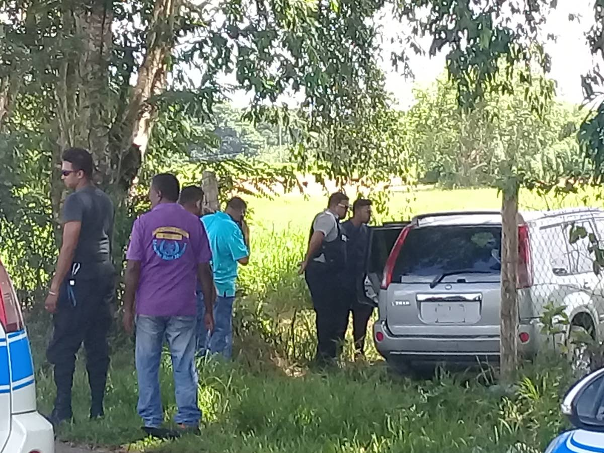 Officers of the Caroni Police Station examine a silver Nissan X Trail with missing license plate numbers which was believed to have been used as the getaway vehicle in a St Helena bank robbery yesterday.
