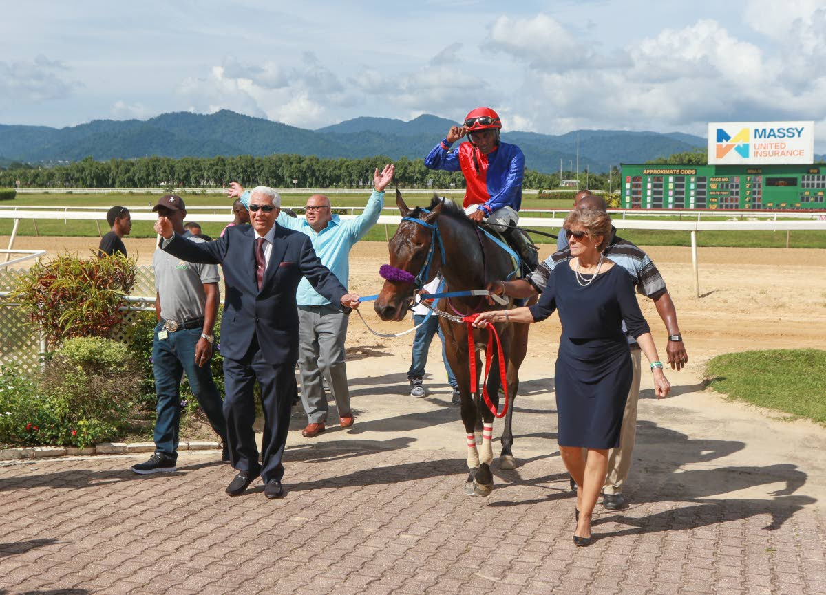 The connections of 'Cape Canaveral' lead the 2018 Carib Brewery Trinidad Derby winner, with jockey Ricardo Jadoo aboard, into the winners circle, at the Santa Rosa Park, Arima yesterday.