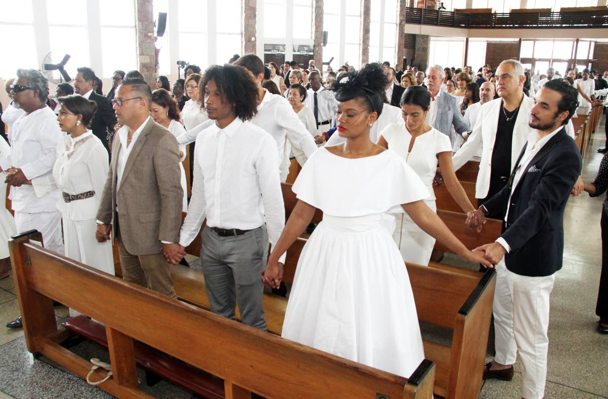 HOLD HANDS: Mourners hold hands in prayer yesterday at the funeral for fashion photographer Calvin French at the Church of the Assumption in Maraval. PHOTO BY SUREASH CHOLAI