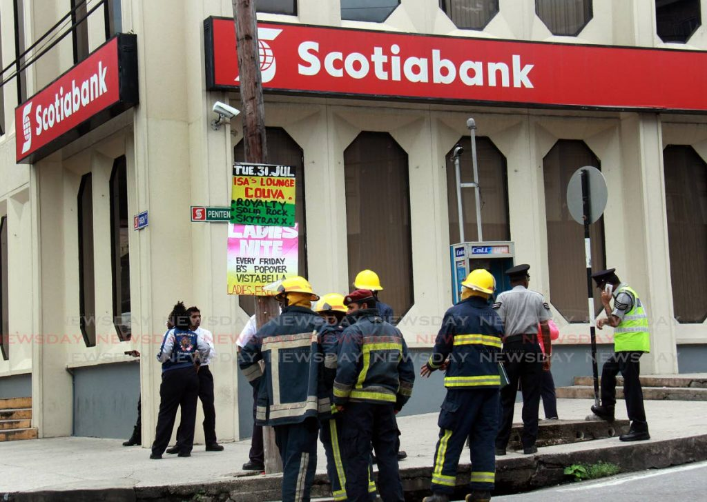 Police and fire officers stand outside of Scotiabank on High Street, San Fernando during a bomb scare at the bank. PHOTO BY ANIL RAMPERSAD.