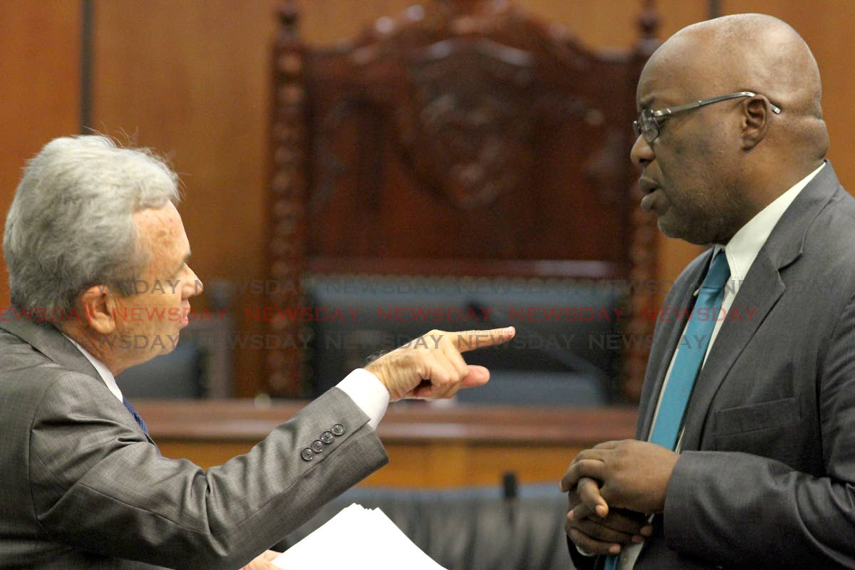 Finance Minister Colm Imbert, left, speaks with Chief Secretary Kelvin Charles in Parliament last month.