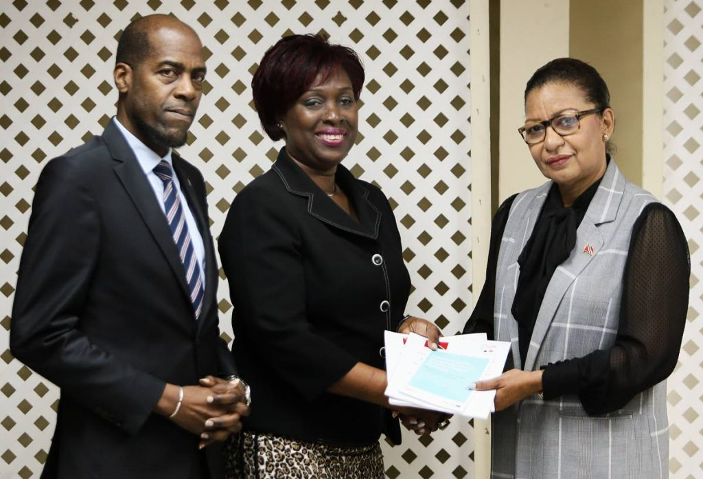 Monica Paula Mc Lean  Project Manager Delegation of the European Union to TT (centre) presents copies of a report to Minister in the Ministry of National Security Glenda Jennings - Smith as Permanent Secretary in the Ministry Vel Lewis looks on. PHOTO BY AZLAN MOHAMMED
