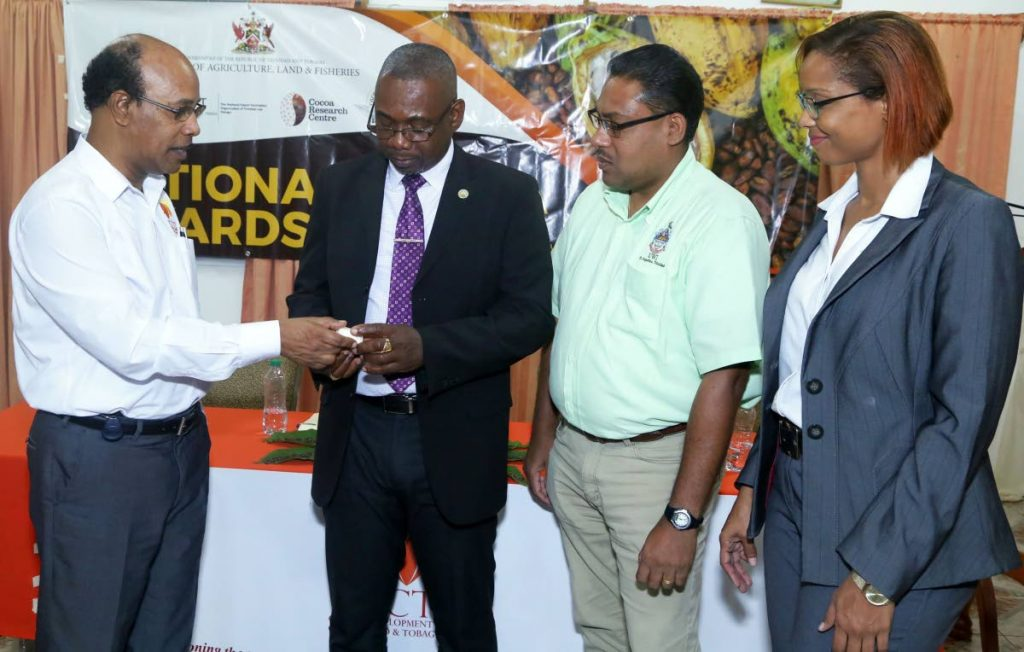 Food Production Secretary Hayden Spencer, second from left, shares information with, CEO of the Cocoa Development Company of TT, Leon Granger, at left, while UWI's Cocoa Research Centre' Director, Dr Darin Sukha, and Marketing Manager, Cocoa Development Company,  Gabriella Gonzales look on at last Thursday's launch of the National Cocoa Awards competition at the Blenheim Sheep Multiplication and Research project in Blenheim.