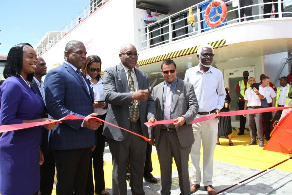 Chief Secretary Kelvin Charles, third from right, with help from Transport Minister Rohan Sinanan, second from right, cuts the ribbon to welcome the Galleons Passage on the sea bridge at the end of its first official sailing on Monday at the Scarborough port.  Also participating in the event are, from left, Tourism Secretary Nadine Stewart-Phillips, Finance Secretary Joel Jack and NIDCO Chairman Herbert George PHOTO SUREASH CHOLAI