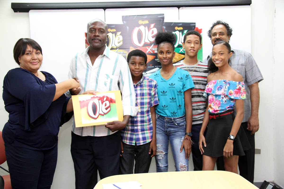 Michelle Agostini Sunshine Snacks Brand Manager,left,  presents a cheque for 50 uniforms to the Silver Bullet Athletic Club head coach Kenrick Williams,2nd left, while club members Jemell Boatswain, Camille Lewis , Reuel Lewis , Christimarie Maharaj and assistant coach Chris Maharaj look on at the ABIL Head Office, San Juan. Photo by Sureash Cholai