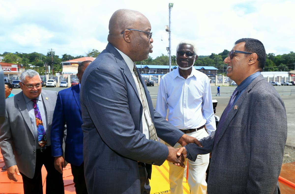 Works and Transport Minister Rohan Sinanan right, greets Chief Secretary Kevin Charles on Monday at the Scarborough port following the docking of the Galleons Passage on its first official journey on the sea bridge. Photo by SUREASH CHOLAI