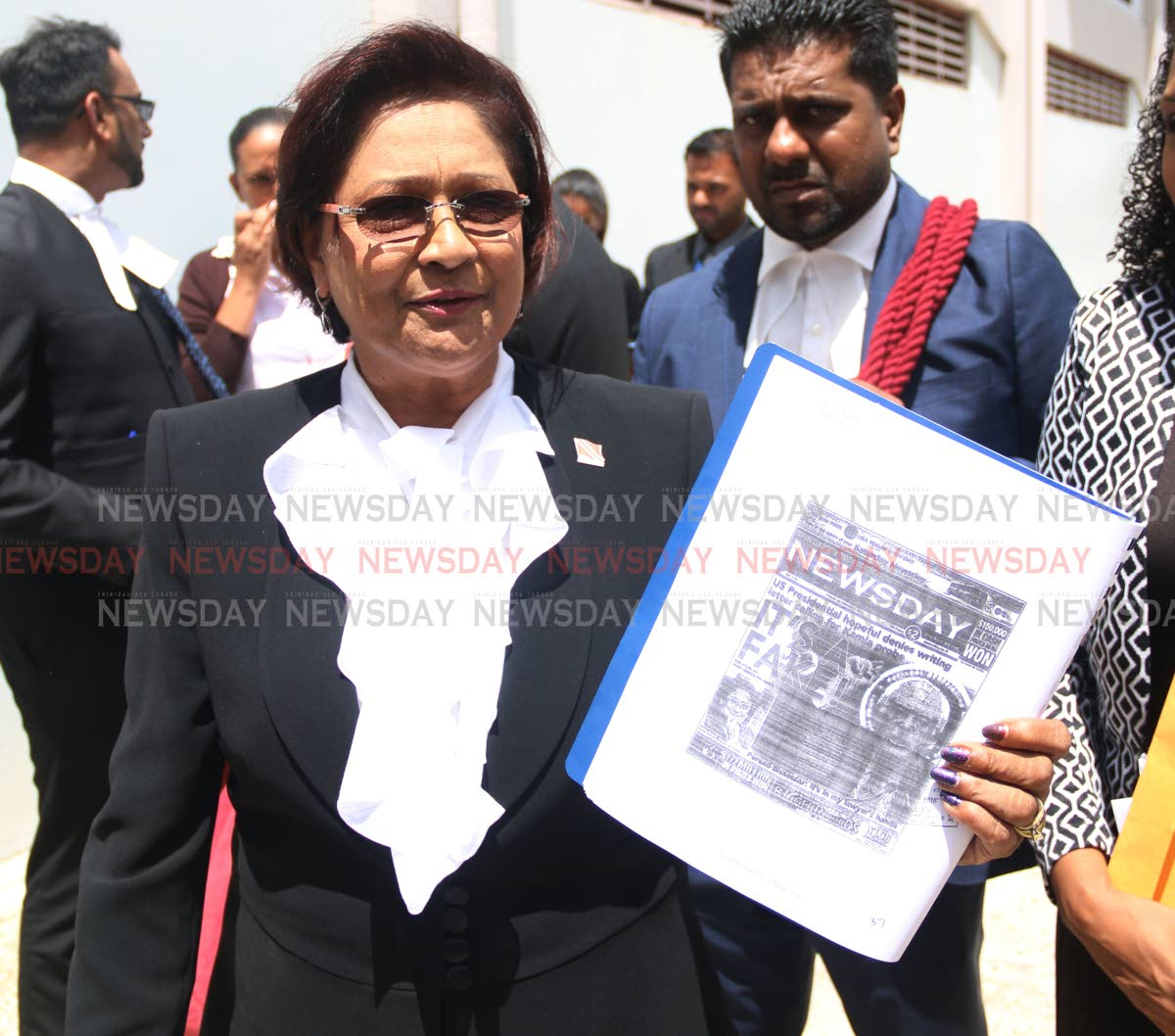 Oppostion Leader Kamla Persad-Bissessar was seen holding up the copy of a front page of Newsday which reads