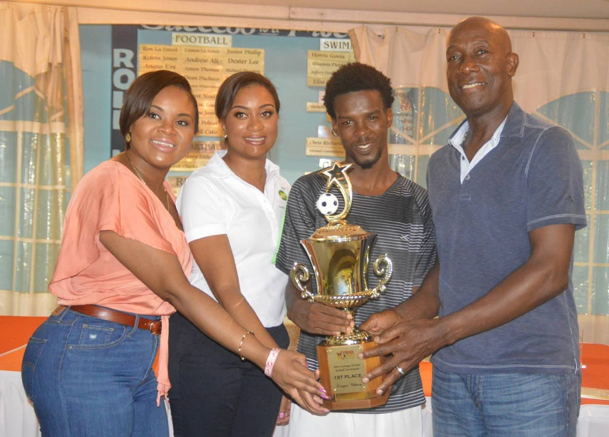 Micah Lansiquot, second from right, captain of Mt Pleasant FC, league champions of the 2018 BPTT-sponsored Carenage All-Star Football League, proudly displays the championship trophy, with Prime Minister Dr Keith Rowley, right, Minister of Sport and Youth Affairs Shamfa Cudjoe, left, and Rachael Caines, BPTT representative.
