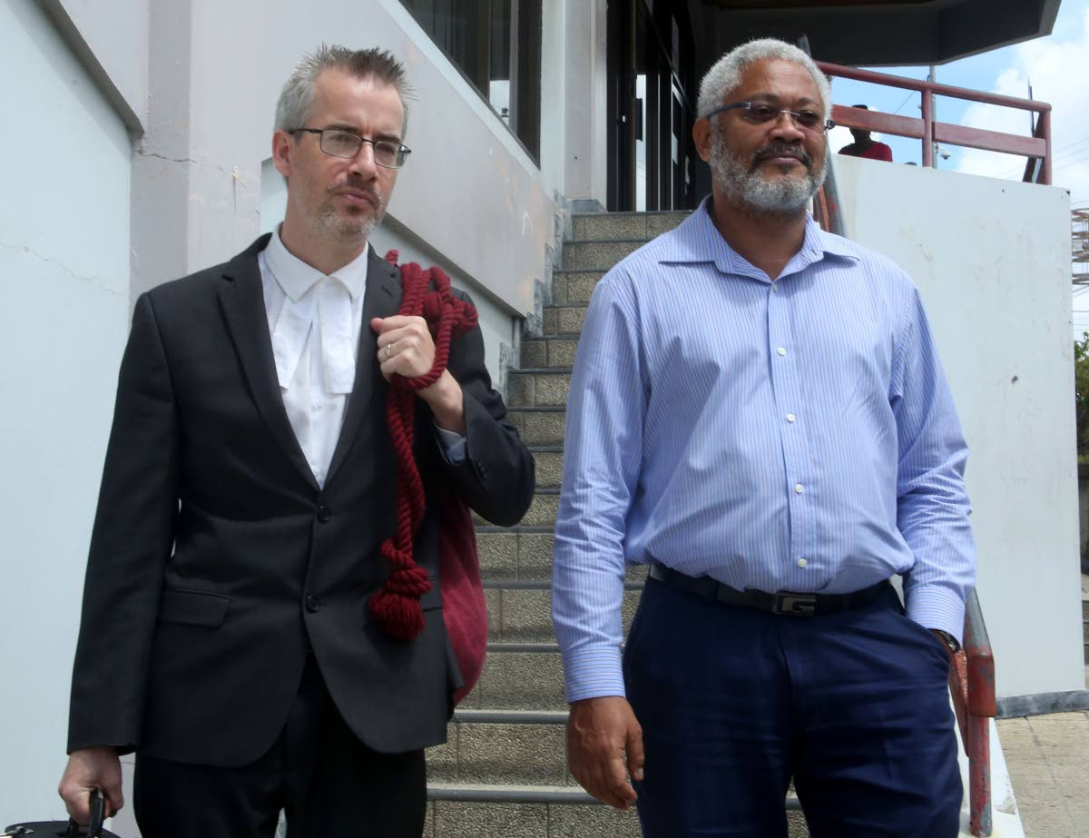 Consultant surveyor Afra Raymond leaves San Fernando High Court this morning with his attorney Kingsley Walesby after winning the right to have information on government's deal with Sandals resort. Photo by Vashti Singh