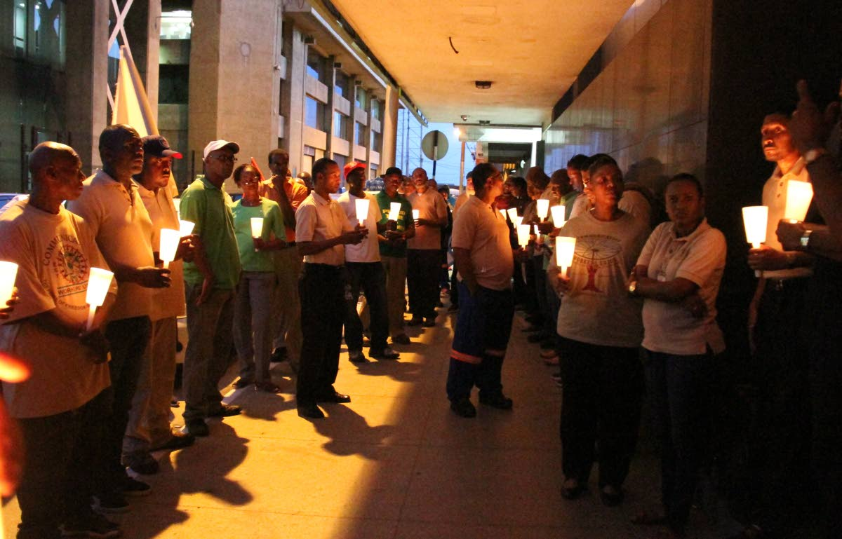 LET THERE BE LIGHT: Communications Workers Union members and other trade union comrades hold lit candles during a vigil outside TSTT House on Lower Edward Street in Port of Spain yesterday evening. PHOTO BY SUREASH CHOLAI